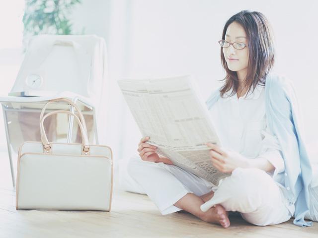 床に座って新聞を読む女性