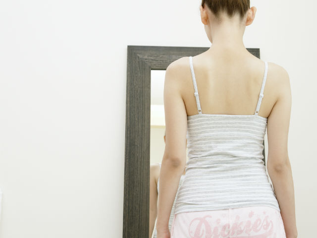 鏡の前に立つ女性