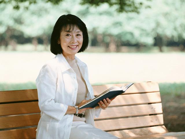 ベンチに座り本を読む女性