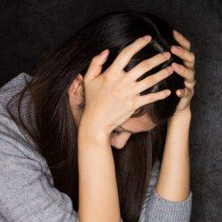 頭の痛みを耐える女性